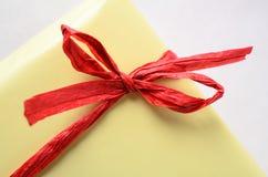 Arc rouge de raphia sur le paquet enveloppé par cadeau jaune Photographie stock
