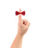 Arc rouge sur le doigt. image stock