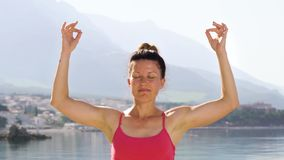 Arc shot of adult woman closed her eyes practicing yoga at mediterranean seaside. Relaxing, meditation outdoors, practicing peace of mind. people, fitness and stock video footage