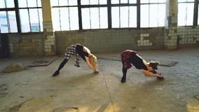 Arc shot of two women dancers stretching in hall of old factory with lens flare. Effect. hobby, choreography, contemporary dance stock video footage