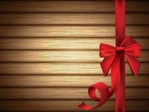 Arc soyeux rouge avec le ruban au-dessus du fond en bois Photos libres de droits