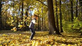 Arc tiré de la petite fille mignonne jetant les feuilles jaunes dans le ciel en parc d'automne banque de vidéos