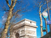 Paris Arc de Triomphe & Bus Stop signs Place Etoile France. The Arc of triomphe with winter trees and blue sky. Part of a bus stop shelter and bus signs. Place Royalty Free Stock Photo