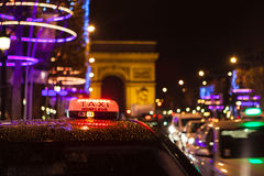 Arc of Triumph. In Avenue of Champs-Elysees at night with selective focus on the taxi in the first plan Stock Photo