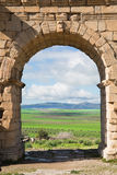 Arc at Volubilis, ancient roman city in Morocco. Through it is visible the fertile and green moroccan country Stock Photos