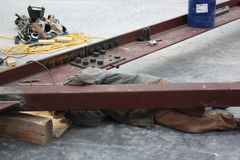 A Welder Welding Angle Brace to Truss Joist. An arc-welder performs an `overhead` weld while lying on his back Stock Images