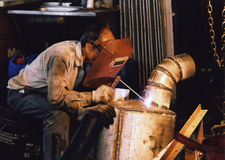 Arc welder at work #2. A worker beginning to weld in a toolshop royalty free stock photography