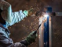 Arc welder worker in protective mask welding metal construction. Heavy industry welder worker in protective mask hand holding arc welding torch working on metal Royalty Free Stock Photos