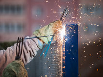 Arc welder worker in protective mask welding metal construction. Heavy industry welder worker in protective mask hand holding arc welding torch working on metal Royalty Free Stock Photography