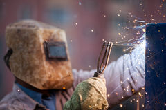 Arc welder worker in protective mask welding metal construction. Heavy industry welder worker in protective mask hand holding arc welding torch working on metal Stock Photo