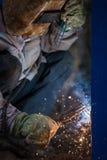 Arc welder worker in protective mask welding metal construction. Heavy industry welder worker in protective mask hand holding arc welding torch working on metal Royalty Free Stock Images