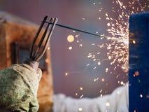 Arc welder worker in protective mask welding metal construction. Heavy industry welder worker in protective mask hand holding arc welding torch working on metal Royalty Free Stock Image