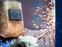 Arc welder worker in protective mask welding metal construction. Heavy industry welder worker in protective mask hand holding arc welding torch working on metal Stock Image