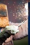 Arc welder worker in protective mask welding metal construction. Heavy industry welder worker in protective mask hand holding arc welding torch working on metal Stock Photos