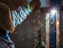 Arc welder worker in protective mask welding metal construction. Heavy industry welder worker in protective mask hand holding arc welding torch working on metal Stock Photo