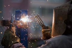 Arc welder worker in protective mask welding metal construction Stock Image