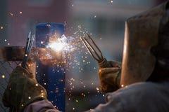 Arc welder worker in protective mask welding metal construction. Heavy industry welder worker in protective mask hand holding arc welding torch working on metal Stock Image
