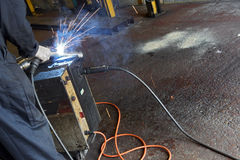 Arc welding. Welder at work arc welding a pipe together Royalty Free Stock Photography