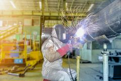 Arc welding. Worker welding metal piping using arc welder and wear equipment protection mask in factory Royalty Free Stock Photography