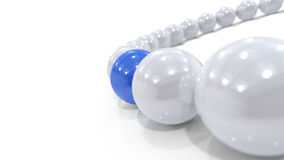 Arc of white orbs with one blue Royalty Free Stock Photos