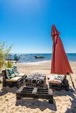 Arcachon Bay, French Atlantic Coast. Red beach umbrella on the Arcachon Bay, France, table and sofas on the beach Royalty Free Stock Images