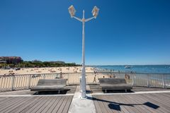Arcachon, France. The central beach and the jetty. The beach in summer seen from the jetty Thiers, with public benches and typical street light Stock Photos