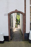 Arcada do tijolo na parede que conduz para jardinar Imagens de Stock