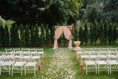 Arcada hermosa de la boda Arco adornado con el paño y las flores amelocotonados Foto de archivo libre de regalías