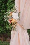 Arcada hermosa de la boda Arco adornado con el paño y las flores amelocotonados Fotos de archivo libres de regalías