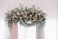 Arcada hermosa de la boda Arco adornado con el paño y las flores amelocotonados y plateados Imagen de archivo