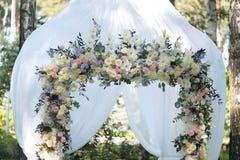 Arcada hermosa de la boda Arco adornado con el paño y las flores blancos Fotografía de archivo