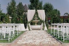 Arcada hermosa de la boda Arco adornado con el paño y las flores del biege Foto de archivo libre de regalías