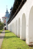 Arcade of the ancient courtyard of Spaso-Prilutsky Monastery at summer sunny day in in the Vologda, Russia. Blue sky and green grass. Castle defense wall Stock Photography