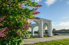 Arcade of the ancient trade marketplace in Veliky Novgorod, Russia. Blurred view of Yaroslav's courtyard and Kremlin with blooming lilac  (focus at the lilac) on Stock Photography