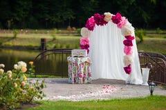 Arcade blanche romantique de bas-côté de mariage avec des pétales de rose, fleurs a Photographie stock