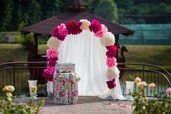 Arcade blanche romantique de bas-côté de mariage avec des pétales de rose, fleurs a Photographie stock libre de droits