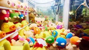 Arcade claw crane machine. Robotic claw crane game machine with toys in arcade Stock Photo
