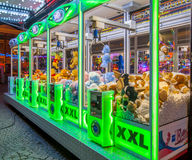 Arcade crane green. GRONINGEN, THE NETHERLANDS-MAY 5, 2015: Arcade crane vending machine with colourful green lights on the annual funfair on central square Royalty Free Stock Photo