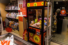 Arcade Crane Machine. An arcade crane filled with cute fluffy gifts placed to the exit section next to checkout counters inside of a supermarket located in Royalty Free Stock Photo