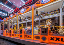 Arcade crane orange. GRONINGEN, THE NETHERLANDS-MAY 5, 2015: Arcade crane vending machine with colourful orange lights on the annual funfair on central square Royalty Free Stock Images