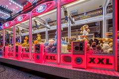 Arcade crane pink. GRONINGEN, THE NETHERLANDS-MAY 5, 2015: Arcade crane vending machine with colourful pink lights on the annual funfair on central square Stock Photos