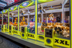 Arcade crane yellow. GRONINGEN, THE NETHERLANDS-MAY 5, 2015: Arcade crane vending machine with colourful yellow lights on the annual funfair on central square Stock Photos