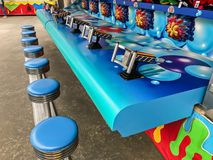 Arcade game. Empty stools at an arcade game where people are shooting water into a small hole competing to win a stuffed animal Stock Images