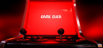Arcade Game Game Over. A vintage arcade game machine with a bright red illuminated screen that reads game over in white on a dark arcade background Stock Photography