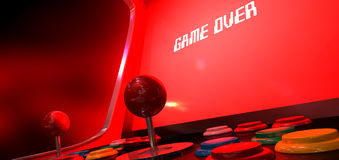 Arcade Game Game Over. A vintage arcade game machine with a bright red illuminated screen that reads game over in white on a dark arcade background Royalty Free Stock Photos