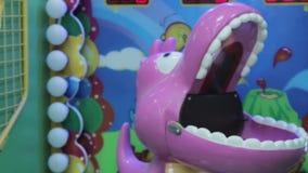Arcade game machine at an amusement park, purple. Child playing arcade game machine at an amusement park stock video