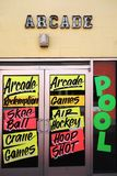 Arcade games signs. Front doors to an arcade with game signs in the window Stock Image