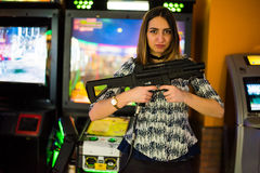 Arcade games. Young brunette long haired girl holding an arcade game plastic gun and looking challenging at the camera Stock Photo