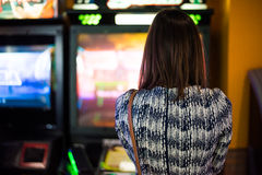 Arcade gaming. Young brunette long haired girl holding an arcade game plastic gun and looking challenging at the camera Royalty Free Stock Image