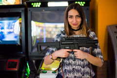 Arcade gun. Young brunette long haired girl holding an arcade game plastic gun and looking challenging at the camera Royalty Free Stock Images